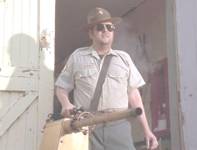 森林警備員が蚊対策の噴煙機材を抱えてドヤ顔