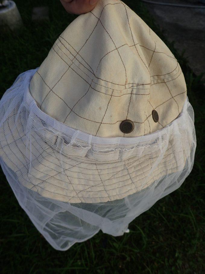 """使い古した帽子に""""虫よけネット""""を取り付ける様子"""