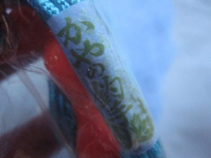 吊り下げ用のヒモを束ねたタグの文字「かやの釣手」