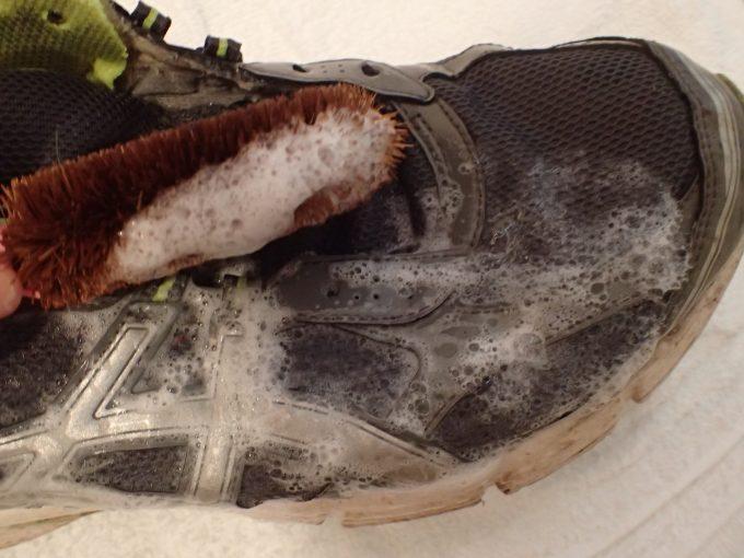汚れた靴をシャンプーを使ってタワシでゴシゴシ洗う
