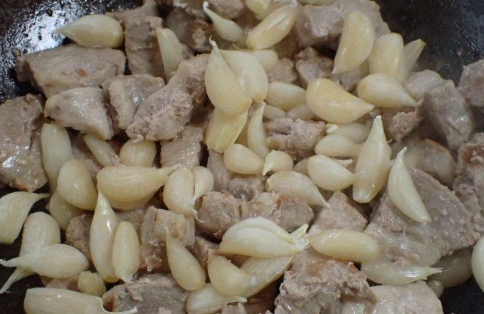 フライパンで肉と生ニンニクを炒める